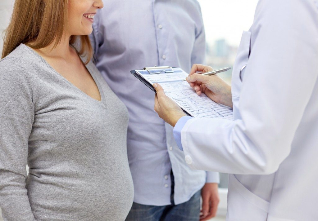 pregnancy, healthcare, people and medicine concept - close up of happy pregnant woman, man and doctor with clipboard at medical appointment in hospital